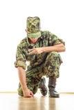 Στρατιώτης στην κάλυψη ομοιόμορφη και καπέλο που γονατίζει στο πάτωμα και Στοκ Φωτογραφίες