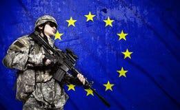 Στρατιώτης στο υπόβαθρο σημαιών της Ευρωπαϊκής Ένωσης Στοκ εικόνες με δικαίωμα ελεύθερης χρήσης