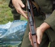 στρατιώτης χρεώνοντας το πυροβόλο όπλο κατά τη διάρκεια μιας προσομοίωσης του πολέμου Στοκ Εικόνες