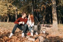 Στρατοπέδευση φθινοπώρου ευτυχές ζεύγος που αγκαλιάζει και που κατασκευάζει το τσάι ή τον καφέ ποτά θερμά Στοκ εικόνα με δικαίωμα ελεύθερης χρήσης