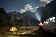 Στρατοπεδεύοντας με ένα αυτοκίνητο, κίτρινη σκηνή στη νύχτα φεγγαριών, άτομο με τον προβολέα στα βουνά στοκ φωτογραφίες