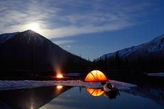 Στρατόπεδο κοντά στη λίμνη βουνών Τοπίο νύχτας με μια σκηνή κοντά στο νερό στοκ εικόνα