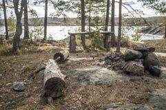 Στρατόπεδο στη δύσκολη ακτή της λίμνης Ένας παλαιός ξύλινος πίνακας, ένα benc Στοκ Φωτογραφίες