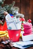 Στριμμένοι λογαριασμοί των δολαρίων και των ευρώ κόκκινα ευρο- και ρόδινων macaroons κάδων Χριστουγέννων, Νέα δώρα έτους ` s Στοκ Εικόνα