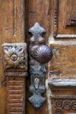 Στρογγυλή λαβή μετάλλων της ενδιαφέρουσας μορφής και της κλειδαριάς στην παλαιά κατασκευασμένη ξύλινη πόρτα Στοκ Εικόνα