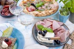 Στρογγυλή μεγάλη πίτσα από το φούρνο με το prosciutto και τις ελιές, το arugula και το βασιλικό Πίνακας που θέτει για το μεσημερι Στοκ Φωτογραφίες