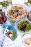 Στρογγυλή μεγάλη πίτσα από το φούρνο με το prosciutto και τις ελιές, το arugula και το βασιλικό Πίνακας που θέτει για το μεσημερι Στοκ Φωτογραφία