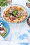 Στρογγυλή μεγάλη πίτσα από το φούρνο με το prosciutto και τις ελιές, το arugula και το βασιλικό Πίνακας που θέτει για το μεσημερι Στοκ Εικόνα