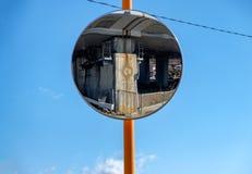 Στρογγυλευμένη κυκλοφορία σημάτων γυαλιού αντανάκλαση στο μπλε ουρανό Στοκ εικόνα με δικαίωμα ελεύθερης χρήσης