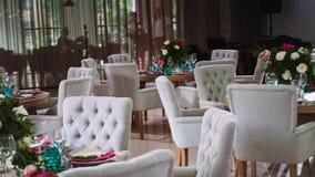 Στρογγυλοί ξύλινοι πίνακες που διακοσμούνται με τις floral ρυθμίσεις που γίνονται από τα άσπρα πιάτα με τις ρόδινες πετσέτες γύρω φιλμ μικρού μήκους