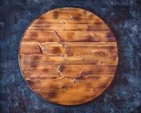 Στρογγυλός κενός ξύλινος τέμνων πίνακας σε ένα σκούρο γκρι κατασκευασμένο υπόβαθρο Τοπ όψη διάστημα αντιγράφων Στοκ Εικόνα