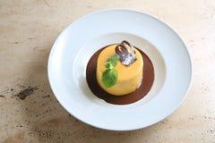 Στρογγυλό κέικ με τη συγκρατημένη σοκολάτα στο άσπρο πιάτο Στοκ εικόνα με δικαίωμα ελεύθερης χρήσης