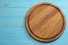 Στρογγυλό ξύλινο πιάτο στην μπλε ξύλινη τοπ άποψη υποβάθρου Στοκ Εικόνα