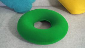 Στρογγυλό πράσινο ορθοπεδικό μαξιλάρι στενό στον επάνω καναπέδων απόθεμα βίντεο