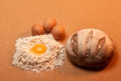 Στρογγυλό ψωμί, τρία αυγά και ένας λέκιθος αυγών που περιβάλλεται από το αλεύρι Στοκ Εικόνες