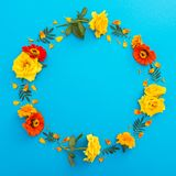 Στρογγυλό floral πλαίσιο των κίτρινων και πορτοκαλιών λουλουδιών στο μπλε υπόβαθρο Επίπεδος βάλτε, τοπ άποψη λεπτομερές ανασκόπησ Στοκ φωτογραφίες με δικαίωμα ελεύθερης χρήσης