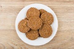 Στρογγυλά καφετιά μπισκότα στο άσπρο πιάτο στον ξύλινο πίνακα Στοκ Φωτογραφίες