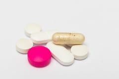 Στρογγυλά χάπια και ωοειδείς σκληρές κάψες στο άσπρο υπόβαθρο Στοκ Φωτογραφίες