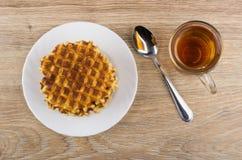 Στρογγυλές βάφλες στο άσπρο πιάτο, το φλυτζάνι του τσαγιού και το κουταλάκι του γλυκού Στοκ φωτογραφία με δικαίωμα ελεύθερης χρήσης