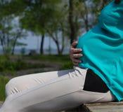 Στρογγυλή μεγάλη κοιλιά μιας εγκύου γυναίκας, στην αναψυχή πάρκων, αποκατάσταση Στοκ φωτογραφίες με δικαίωμα ελεύθερης χρήσης