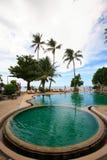 Στρογγυλή πισίνα άποψης θάλασσας, αργόσχολοι ήλιων δίπλα στον κήπο και τον ωκεάνιο ορίζοντα στοκ φωτογραφίες