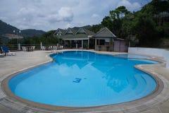 Στρογγυλή πισίνα, αργόσχολοι ήλιων δίπλα στον κήπο και κτήρια στοκ φωτογραφία με δικαίωμα ελεύθερης χρήσης