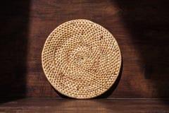 Στρογγυλός δίσκος ινδικού καλάμου ύφανσης, οικογένεια επαρχίας, στο αναδρομικό ξύλινο υπόβαθρο με τη σκιά και τη σκιά, περιβάλλον Στοκ Φωτογραφία