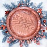 Στρογγυλός ξύλινος δίσκος που περιβάλλεται με τις διακοσμήσεις Χριστουγέννων στο χιόνι Στοκ Εικόνα