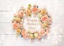 Στρογγυλό πλαίσιο των τριαντάφυλλων με το μήνυμα ημέρας μητέρων σε ένα λευκό ξύλινο Στοκ Φωτογραφίες