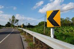 Στροφή του αριστερού σημαδιού κυκλοφορίας στο δρόμο Στοκ Εικόνες