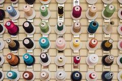 Στροφία της ένωσης νημάτων σε ένα κατάστημα ραφτών Τα νηματοδέματα για τη ράβοντας μηχανή κρεμούν σε ένα ράβοντας κατάστημα στοκ εικόνες