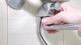 Στροφίγγων μπανιέρων, που σφίγγει το καρύδι σε έναν κρουνό ντους, τις επισκευές υδραυλικών και την έννοια DIY απόθεμα βίντεο