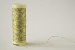 Στροφίο του χρυσού νήματος στο άσπρο υπόβαθρο Στοκ εικόνα με δικαίωμα ελεύθερης χρήσης