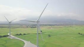 Στρόβιλος αιολικής ενέργειας στο πράσινο τοπίο τομέων και βουνών Εναέριος στρόβιλος ανεμόμυλων άποψης στο σταθμό παραγωγής ηλεκτρ φιλμ μικρού μήκους