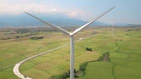 Στρόβιλος ανεμόμυλων στο πράσινο γεωργικό τοπίο τομέων και βουνών Ανεμοστρόβιλος άποψης κηφήνων στο σταθμό παραγωγής ηλεκτρικού ρ απόθεμα βίντεο
