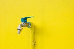 Στρόφιγγα κινηματογραφήσεων σε πρώτο πλάνο στο συγκεκριμένο κίτρινο υπόβαθρο τοίχων Διαρροή νερού Στοκ Φωτογραφίες