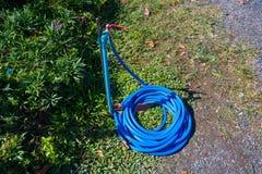 Στρόφιγγα με την μπλε μάνικα στον κήπο Στοκ εικόνες με δικαίωμα ελεύθερης χρήσης