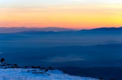 Στρώματα βουνών και ζωηρόχρωμο ηλιοβασίλεμα στο χειμερινό βουνό Στοκ φωτογραφία με δικαίωμα ελεύθερης χρήσης