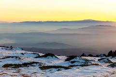 Στρώματα βουνών και ζωηρόχρωμο ηλιοβασίλεμα στο χειμερινό βουνό Στοκ Φωτογραφίες
