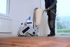 Στρώνοντας με άμμο πάτωμα σκληρού ξύλου με την αλέθοντας μηχανή Στοκ Φωτογραφία