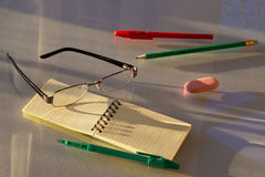 Στυλοί, μολύβι, γόμα και σημειωματάριο με τα γυαλιά στοκ εικόνες