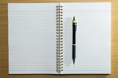 Στυλός, μολύβι και σημειωματάριο στον ξύλινο πίνακα Τοπ όψη Στοκ εικόνα με δικαίωμα ελεύθερης χρήσης
