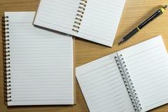 Στυλός, μολύβι και σημειωματάριο στον ξύλινο πίνακα Τοπ όψη Στοκ φωτογραφία με δικαίωμα ελεύθερης χρήσης