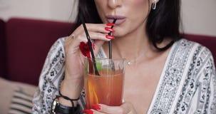 Στόμα κινηματογραφήσεων σε πρώτο πλάνο του θηλυκού προτύπου μόδας που πίνει το φρέσκο κοκτέιλ που χρησιμοποιεί το γυαλί εκμετάλλε απόθεμα βίντεο