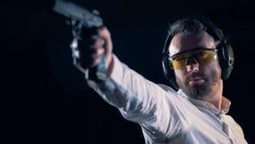 Στόχοι ατόμων, που κρατούν ένα πυροβόλο όπλο σε μια στοά πυροβολισμού, σειρά πυροβολισμού απόθεμα βίντεο