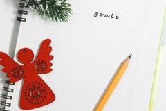 Στόχοι, σημειωματάριο και κίτρινο μολύβι με τον ξύλινο κόκκινο άγγελο Στοκ φωτογραφίες με δικαίωμα ελεύθερης χρήσης