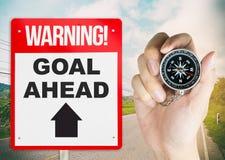 Στόχος προειδοποιητικών σημαδιών μπροστά με την πυξίδα εκμετάλλευσης χεριών Στοκ φωτογραφίες με δικαίωμα ελεύθερης χρήσης