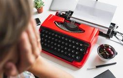 Συγγραφέας γυναικών που εργάζεται σκεπτικά σε ένα βιβλίο στην κόκκινη γραφομηχανή γραφείων της Στοκ Εικόνα