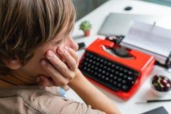 Συγγραφέας γυναικών που εργάζεται σκεπτικά σε ένα βιβλίο στην κόκκινη γραφομηχανή γραφείων της Στοκ φωτογραφίες με δικαίωμα ελεύθερης χρήσης