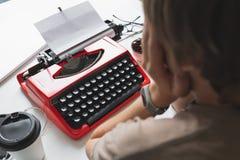 Συγγραφέας γυναικών που εργάζεται σκεπτικά σε ένα βιβλίο στην κόκκινη γραφομηχανή γραφείων της Στοκ εικόνα με δικαίωμα ελεύθερης χρήσης